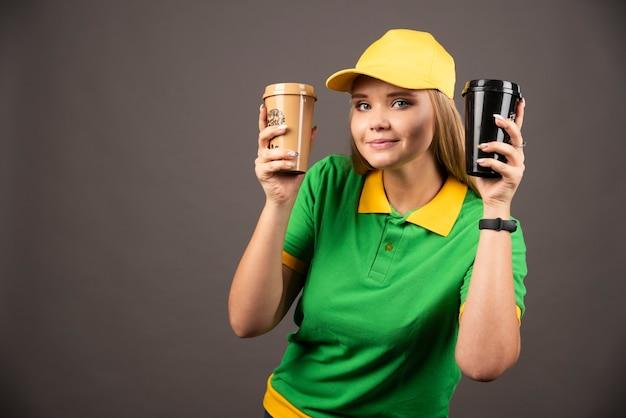 Junge lieferfrau, die tassen kaffee auf schwarzer wand hält.