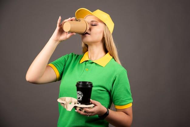 Junge lieferfrau, die von einer tasse kaffee auf schwarzer wand trinkt.