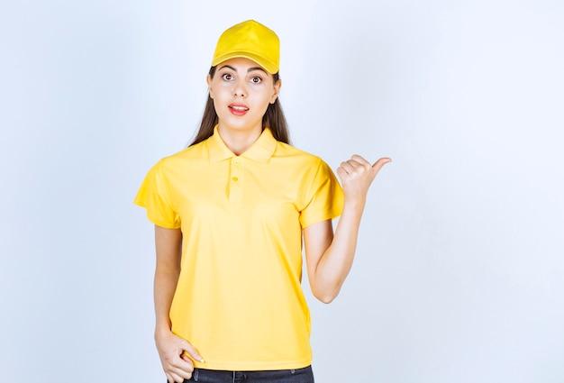 Junge lieferfrau im gelben t-shirt und in der kappe, die irgendwo auf weiß zeigt.