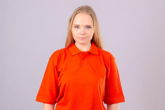 Junge lieferfrau im orangefarbenen poloshirt, das mit lächeln auf gesicht steht, das über lokalisiertem weißem hintergrund steht