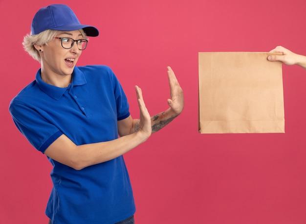Junge lieferfrau in blauer uniform und kappe, die sich weigert, ein papierpaket zu nehmen, das über rosa wand steht