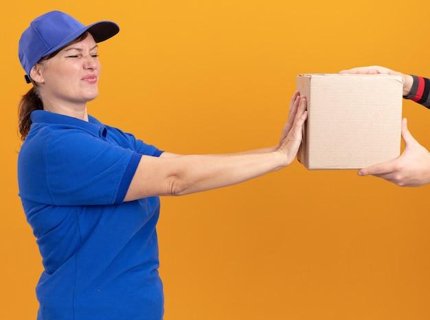 Junge lieferfrau in blauer uniform und mütze, die besorgt mit angewidertem ausdruck schaut und sich weigert, paket zu nehmen, das über orange wand steht
