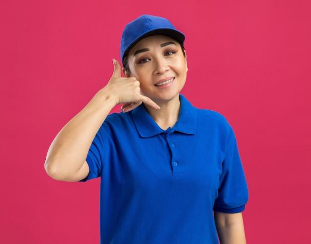 Junge lieferfrau in blauer uniform und mütze, die fröhlich lächelt und mich anruft