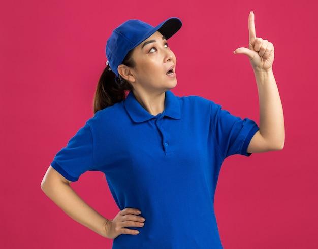 Junge lieferfrau in blauer uniform und mütze, die mit dem zeigefinger nach oben zeigt und neugierig nachdenkt