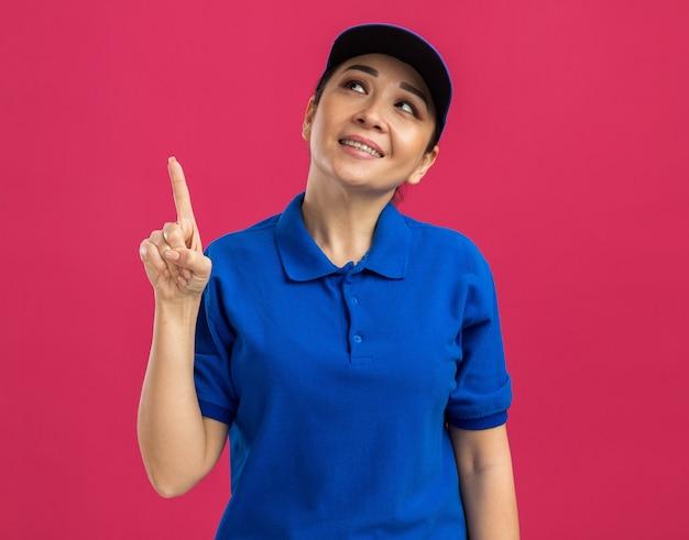 Junge lieferfrau in blauer uniform und mütze, die mit dem zeigefinger nach oben zeigt