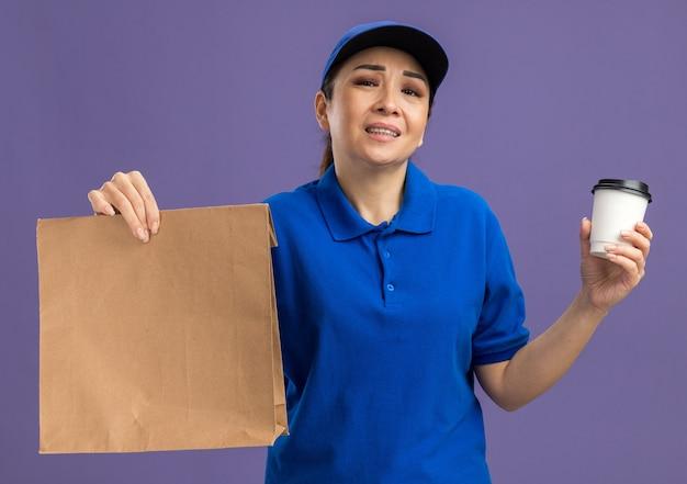 Junge lieferfrau in blauer uniform und mütze, die papierpaket und pappbecher hält, verärgert über traurigen ausdruck, der über lila wand steht