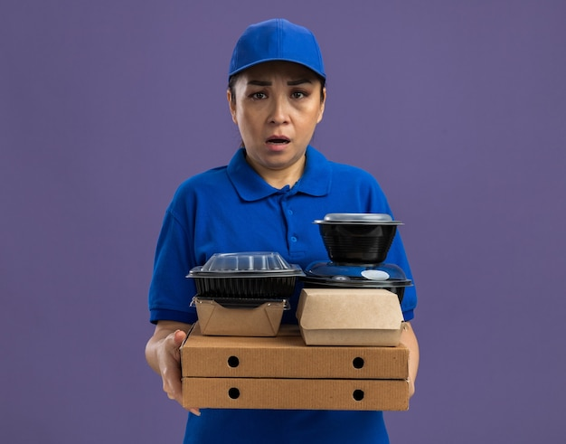 Junge lieferfrau in blauer uniform und mütze, die pizzakartons und lebensmittelpakete mit ernstem stirnrunzeln über der lila wand hält