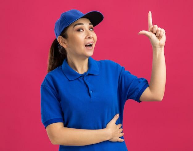 Junge lieferfrau in blauer uniform und mütze lächelt und zeigt mit dem zeigefinger nach oben und hat eine neue idee
