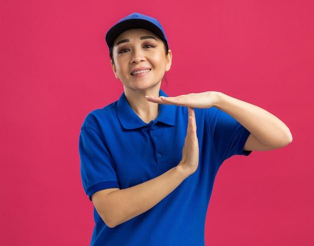 Junge lieferfrau in blauer uniform und mütze mit einem lächeln im gesicht, die eine auszeitgeste mit den händen macht