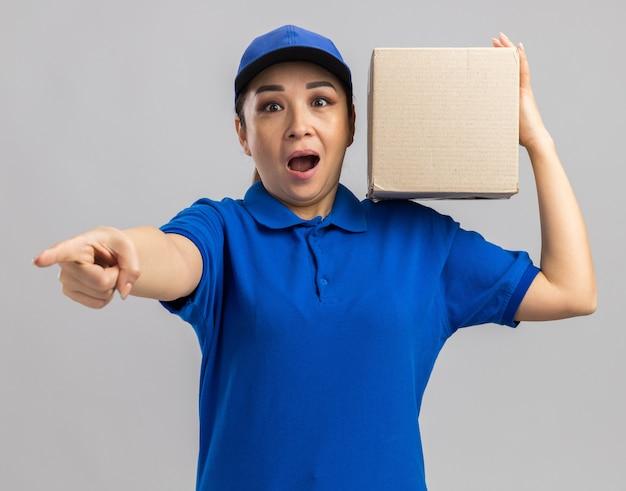 Junge lieferfrau in blauer uniform und mütze mit karton, die überrascht aussieht und mit dem zeigefinger auf die kamera zeigt?