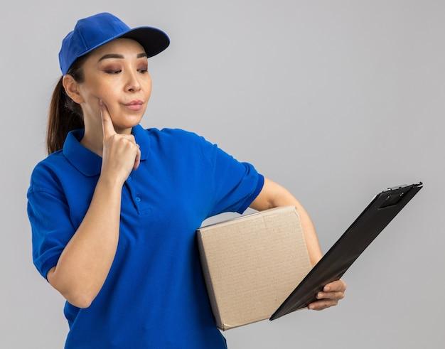 Junge lieferfrau in blauer uniform und mütze mit karton und zwischenablage, die es mit nachdenklichem ausdruck betrachtet, der über weißer wand steht