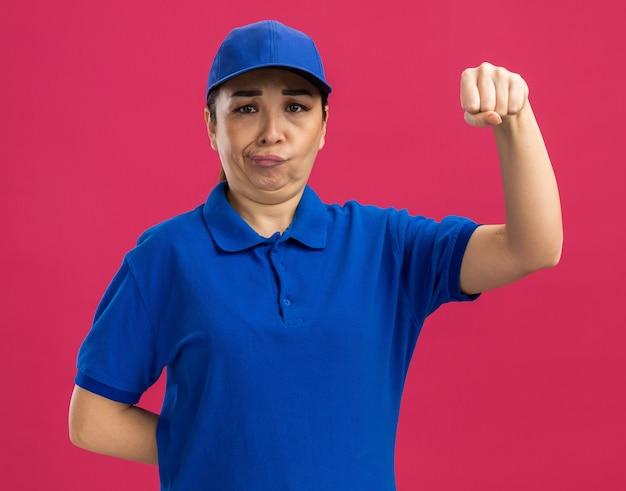 Junge lieferfrau in blauer uniform und mütze verwirrt beim anheben der faust