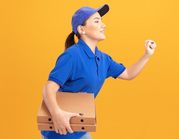 Junge lieferfrau in der blauen uniform und in der kappe, die aufgeregtes ansturmlaufen für das liefern von pizzaschachteln für kunden über orange wand läuft