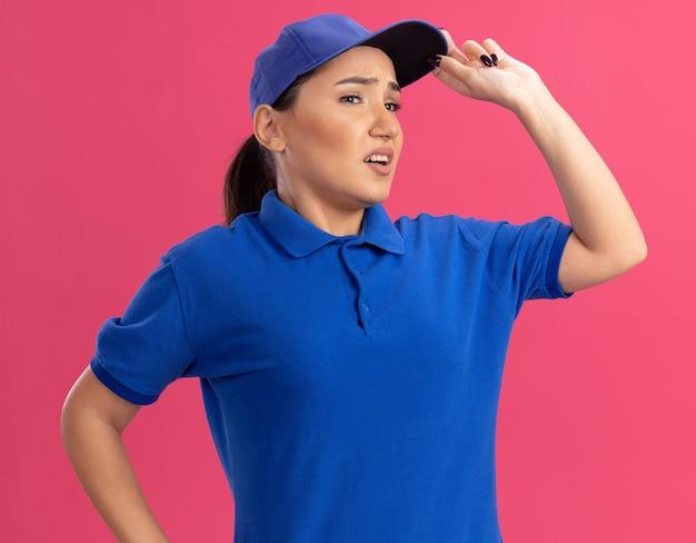 Junge lieferfrau in der blauen uniform und in der kappe, die beiseite schaut verwirrt über rosa wand schaut