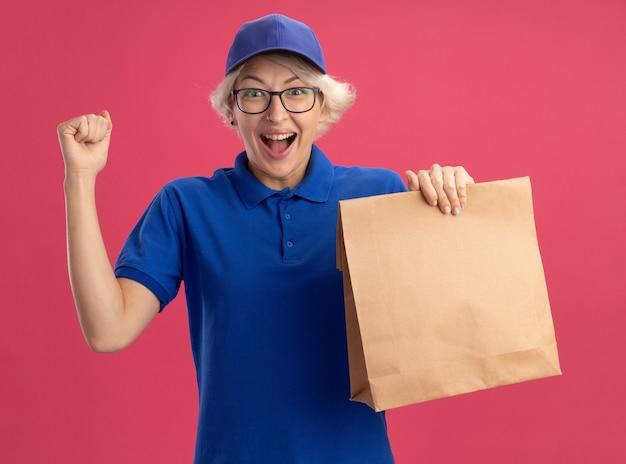 Junge lieferfrau in der blauen uniform und in der kappe, die die brille hält, die papierpaket hält, das faust glücklich und aufgeregt über rosa wand erhebt