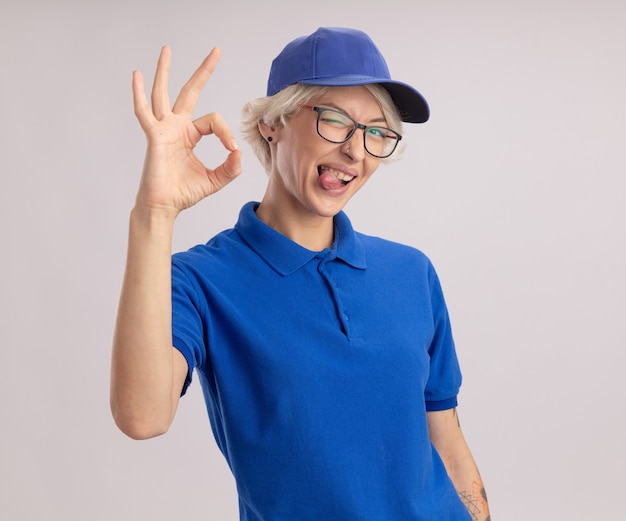 Junge lieferfrau in der blauen uniform und in der kappe, die die brille trägt, die lächelnd lächelnd die zunge herausragt, die über weißer wand steht