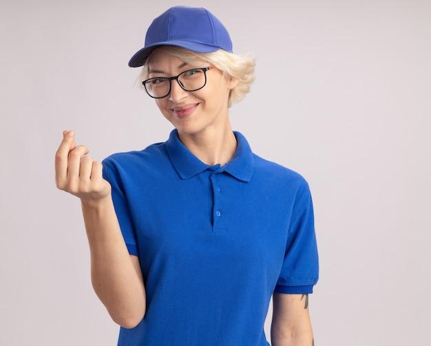 Junge lieferfrau in der blauen uniform und in der kappe, die die brille trägt, die lächelnde reibende finger sieht, die geldgeste machen, die über weißer wand steht