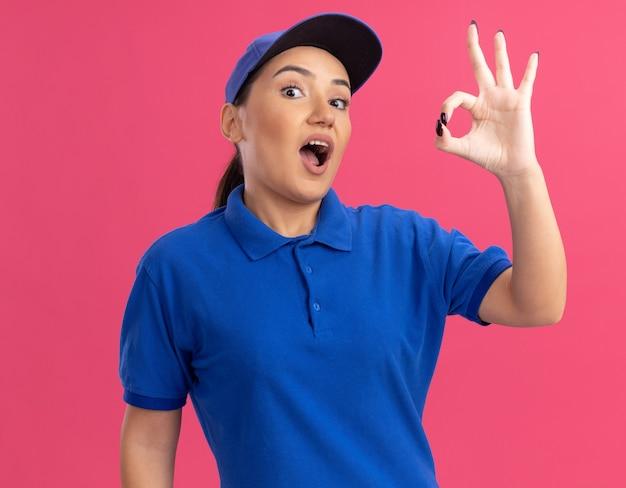 Junge lieferfrau in der blauen uniform und in der kappe, die front glücklich und aufgeregt betrachten, das ok zeichen steht über rosa wand