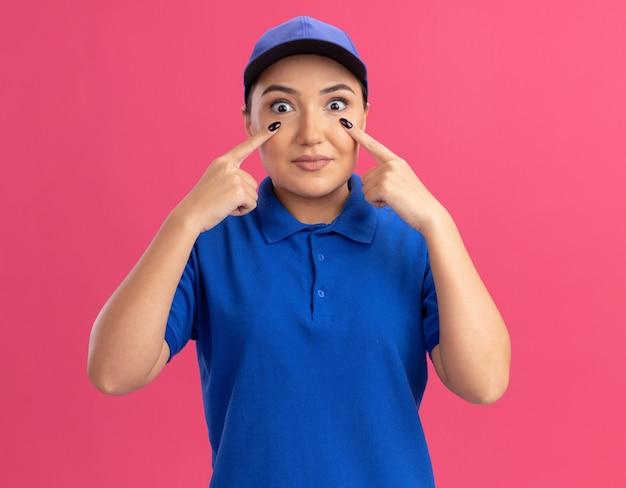 Junge lieferfrau in der blauen uniform und in der kappe, die mit zeigefingern auf ihre augen zeigt, die überrascht stehen, die über rosa wand stehen