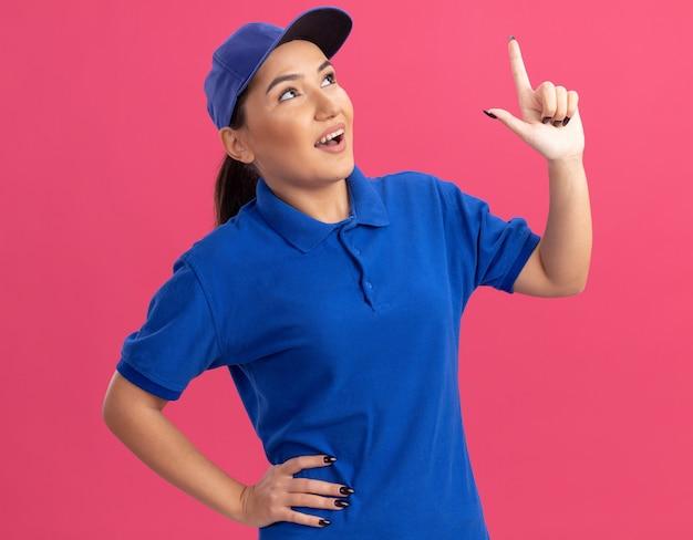 Junge lieferfrau in der blauen uniform und in der kappe, die oben mit zeigefinger auf etwas lächelnd steht, das fröhlich über rosa wand steht