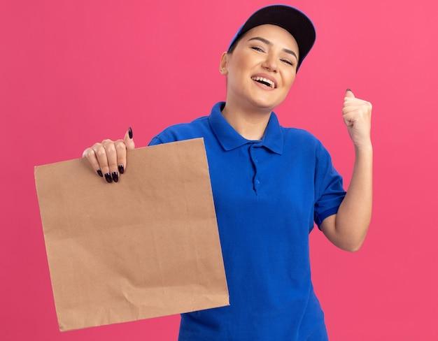Junge lieferfrau in der blauen uniform und in der kappe, die papierpaket glücklich und aufgeregt anhebt, die faust lächelnd freudig stehend über rosa wand