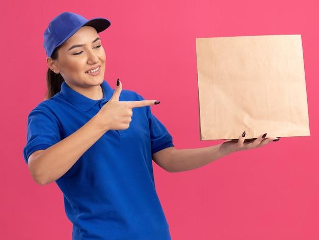Junge lieferfrau in der blauen uniform und in der kappe, die papierpaket hält, das mit dem zeigefinger darauf lächelt, zuversichtlich stehend über rosa wand