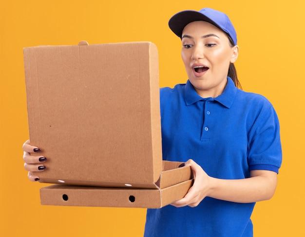 Junge lieferfrau in der blauen uniform und in der kappe, die pizzaschachteln öffnet, die box betrachten, die es erstaunt betrachtet, über orange wand zu stehen