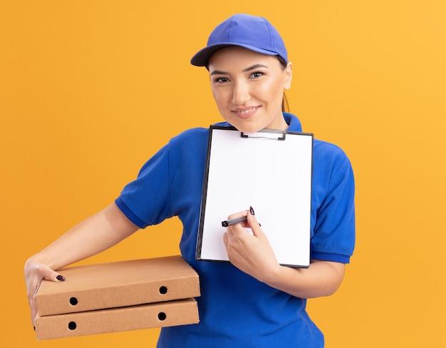 Junge lieferfrau in der blauen uniform und in der kappe, die pizzaschachteln und zwischenablage mit leeren seiten mit bleistift hält, die nach unterschrift fragen, die vorne lächelnd über orange wand steht