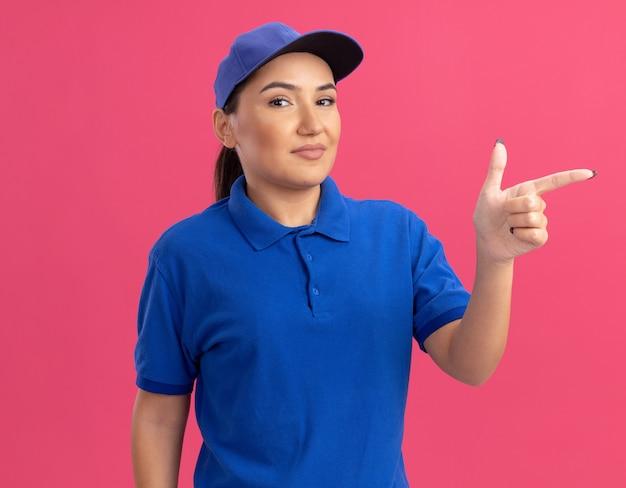 Junge lieferfrau in der blauen uniform und in der kappe, die vorne lächelnd sicheres zeigen mit dem zeigefinger zur seite betrachtet, die über rosa wand steht