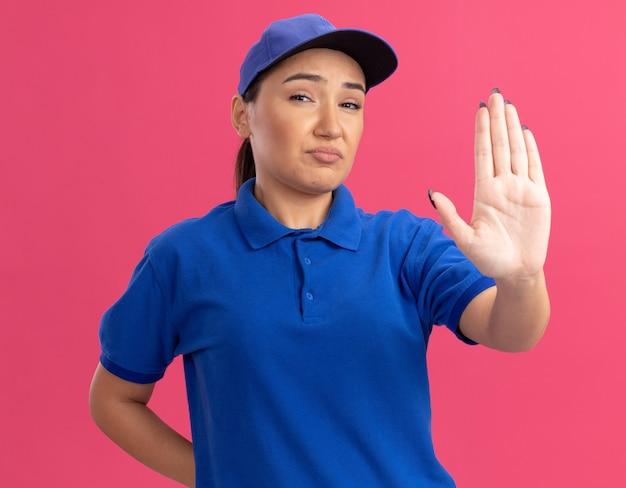 Junge lieferfrau in der blauen uniform und in der kappe, die vorne mit ernstem gesicht schaut, das aufhört, über rosa wand zu stehen