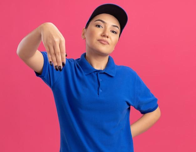 Junge lieferfrau in der blauen uniform und in der kappe, die zuversichtlich gestikulierend mit den händen steht, die über rosa wand stehen