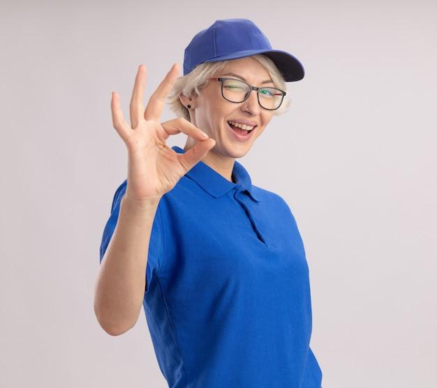 Junge lieferfrau in der blauen uniform und in der kappe, die zwinkernd und lächelnd zeigt okes zeichen, das über weißer wand steht