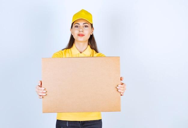 Junge lieferfrau in der gelben kappe, die kartonpaket über weißer wand hält.
