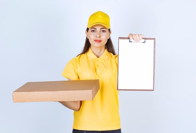 Junge lieferfrau in der gelben kappe, die kartonpaketklemmbrett hält.