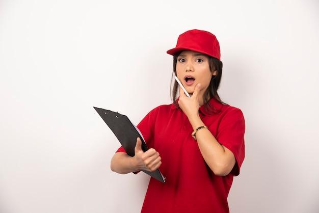 Junge lieferfrau in der roten uniform mit zwischenablage auf weißem hintergrund.
