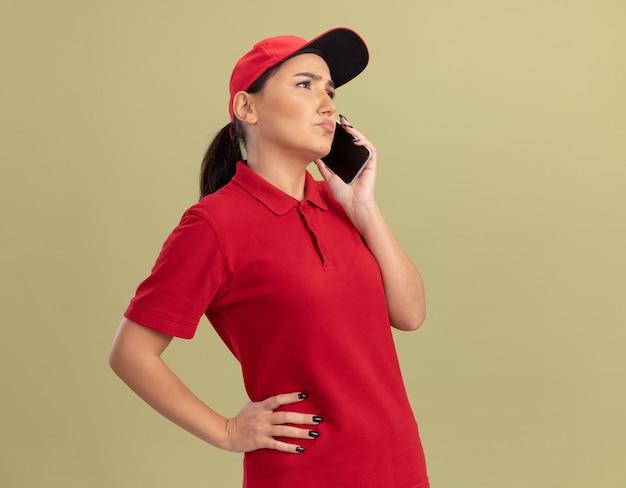 Junge lieferfrau in der roten uniform und in der kappe, die auf handy spricht, der verwirrt steht über grüner wand steht