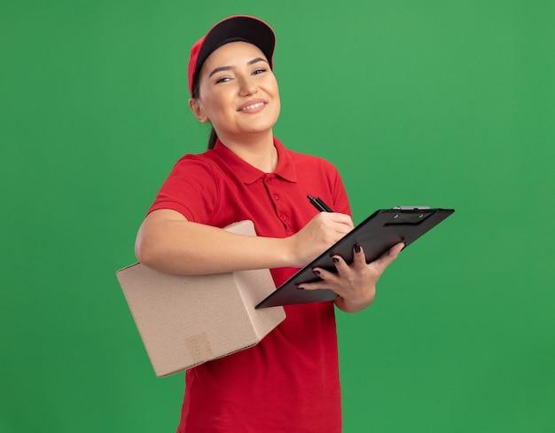 Junge lieferfrau in der roten uniform und in der kappe, die den pappkarton mit der zwischenablage hält, die vorne lächelnd zuversichtlich über grüner wand steht