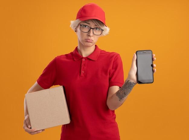 Junge lieferfrau in der roten uniform und in der kappe, die die brille hält, die karton hält, der smartphone mit traurigem ausdruck auf gesicht steht, das über orange wand steht