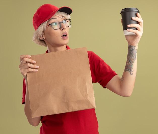 Junge lieferfrau in der roten uniform und in der kappe, die die brille hält, die papierpaket hält, das kaffeetasse in ihrer hand betrachtet, schaut überrascht und erstaunt, über grüner wand stehend