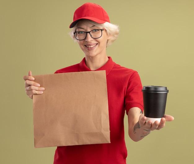 Junge lieferfrau in der roten uniform und in der kappe, die die brille hält, die papierpaket hält, das kaffeetasse lächelnd über grüner wand stehend anbietet
