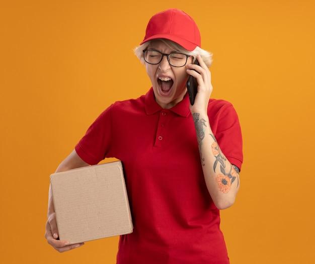 Junge lieferfrau in der roten uniform und in der kappe, die die brille hält, die pappkarton hält, der mit aggressivem ausdruck schreit, während auf handy spricht, das über orange wand steht