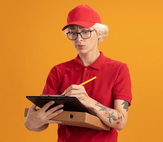 Junge lieferfrau in der roten uniform und in der kappe, die die brille hält, die pizzaschachtel schreibt, die etwas in der zwischenablage schreibt, das verwirrt steht, das über orange wand steht