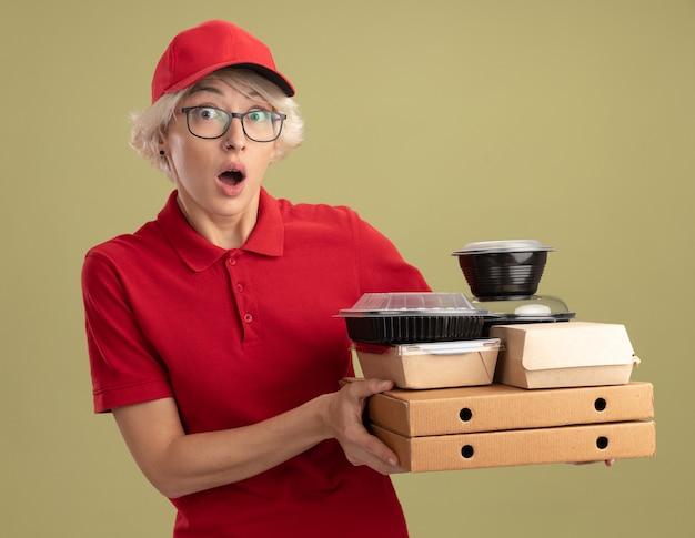 Junge lieferfrau in der roten uniform und in der kappe, die gläser hält, die pizzaschachteln und lebensmittelpakete halten, überrascht und besorgt, über grüner wand stehend