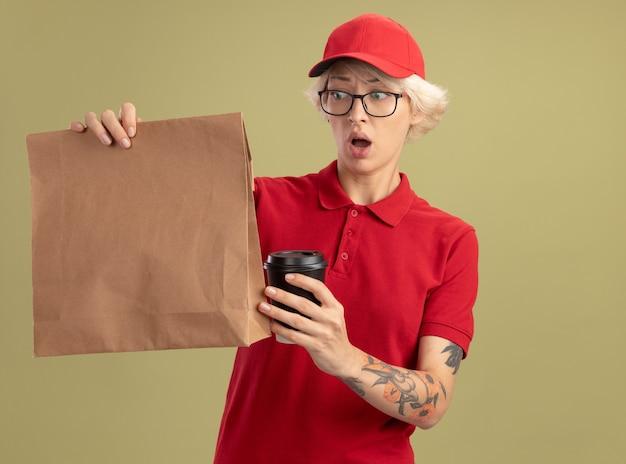 Junge lieferfrau in der roten uniform und in der kappe, die gläser tragen, die papierpaket und kaffeetasse halten, die verwirrt und besorgt stehen über grüner wand stehen
