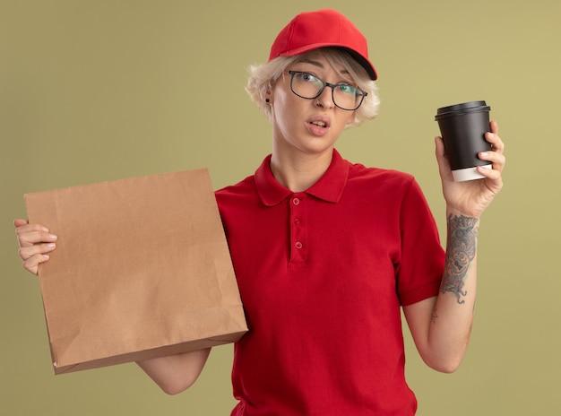 Junge lieferfrau in der roten uniform und in der kappe, die gläser tragen, die papierpaket und kaffeetasse halten verwirrt und sehr besorgt stehen über grüner wand