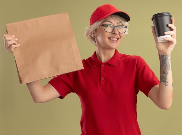 Junge lieferfrau in der roten uniform und in der kappe, die gläser tragen, die papierpaket und kaffeetasse mit dem glücklichen gesicht lächelnd stehen über grüner wand halten