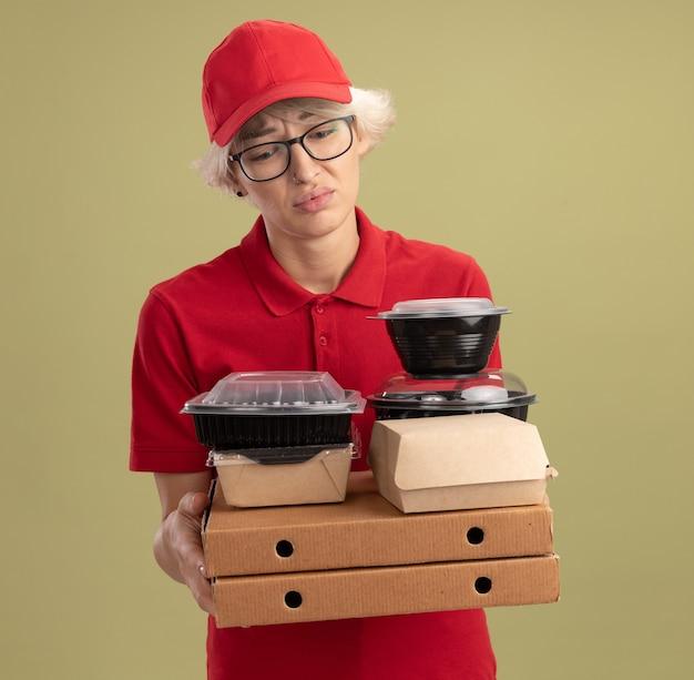 Junge lieferfrau in der roten uniform und in der kappe, die gläser tragen, die pizzaschachteln und nahrungsmittelpakete halten, die mit traurigem ausdruck müde und gelangweilt über grüner wand stehen