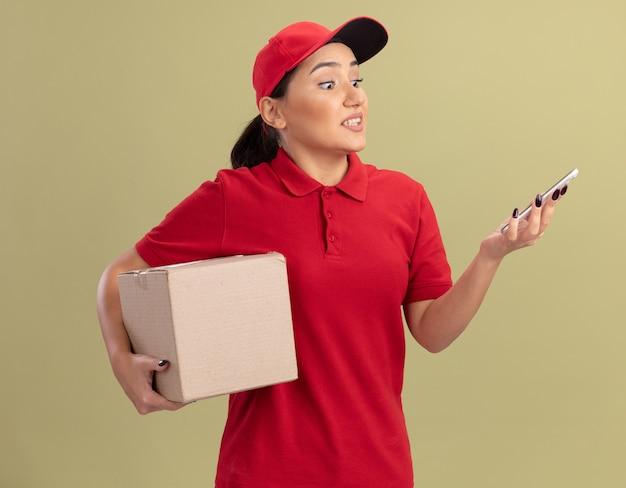Junge lieferfrau in der roten uniform und in der kappe, die karton hält, der ihr smartphone betrachtet, das verwirrt und unzufrieden ist, das über grüner wand steht