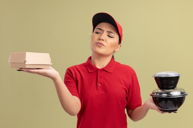Junge lieferfrau in der roten uniform und in der kappe, die lebensmittelpakete halten, die verwirrt und unsicher stehen über grüner wand stehen