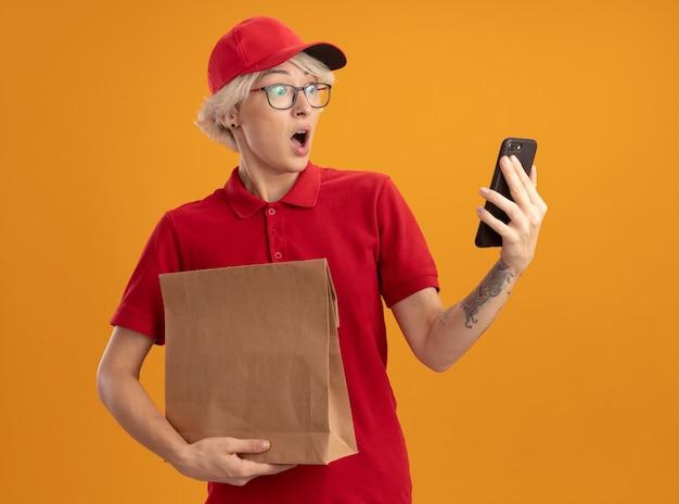 Junge lieferfrau in der roten uniform und in der kappe, die papierpaket hält, das ihr smartphone betrachtet, das verwirrt und überrascht ist, das über orange wand steht